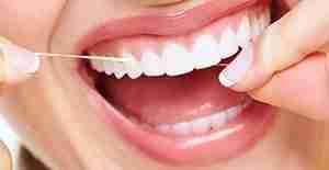 woman flossing dental implants gum disease